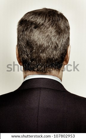 Rear view of the back of a man's head and shoulders. The man is middle aged with graying hair. Background is a stripy wall paper.