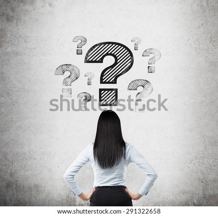 Rear view of the brunette who looks on the drawn question marks. Concrete background. - stock photo