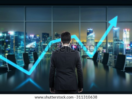 Rear view of the businessman in the office at night time. Rising arrow as a symbol of the success. - stock photo