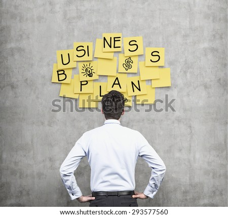 Rear view of the businessman who thinks about new business plan. Yellow stickers are hanged on the concrete wall. - stock photo
