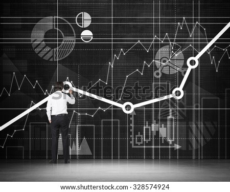 Rear view of the full length person in formal clothes who is drawing analytical graphs on the wall. - stock photo