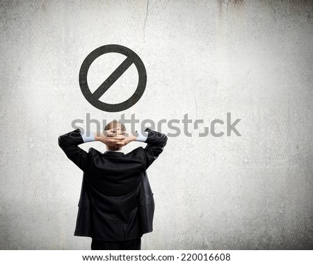Rear view of thoughtful businessman looking at prohibition sign - stock photo