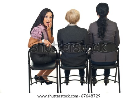 Rear view of three business woman in a row watching  a presentation and one of them returns her head with amazed face isolated on white background