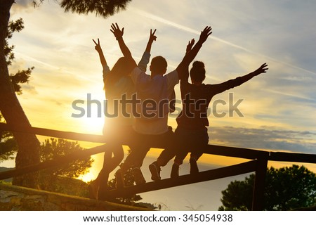 Rear view of three couple best friends travelers put hands up at sunset. Young  relaxing hipster wanderers enjoying exclusive alternative destination. Holiday life moment at warm orange light - stock photo