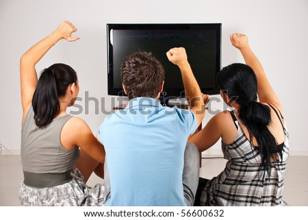 Rear view of three excited  soccer fans sitting on floor and  watching favorite team goal  at tv - stock photo