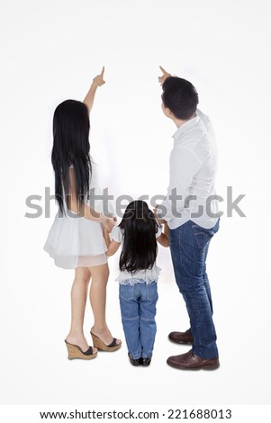 Rear view of three member happy family pointing at copy space in studio