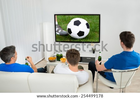 Rear View Of Three Men Sitting On Couch Watching Football Match On Television - stock photo