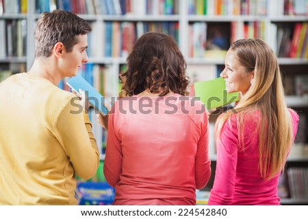 Rear view of three people choosing library books. - stock photo