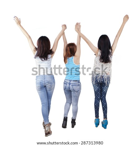 Rear view of three teenage girls holding and raised hands together in the studio