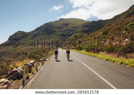 Rear view of two cyclist riding down the country road through mountains. Cycling event of triathlon competition. Triathletes practicing cycling on open country road. - stock photo