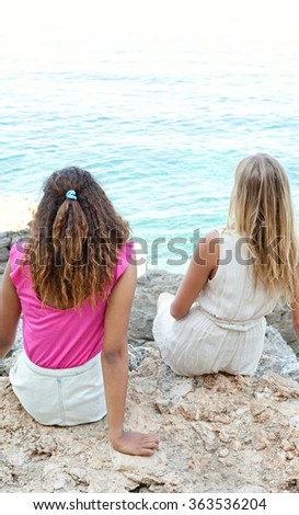 Rear view of two diverse friends, caucasian and african american teenager girls relaxing together on rocks, contemplating the sea, outdoors. Healthy well being adolescents, holiday travel lifestyle. - stock photo