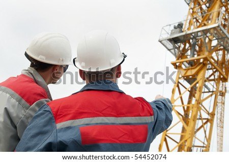 Rear view of two engineer builders at construction site directing to the tower crane - stock photo