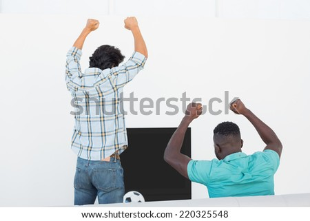 Rear view of two excited soccer fans cheering while watching tv - stock photo