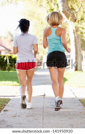 Rear View Of Two Female Runners On Suburban Street - stock photo