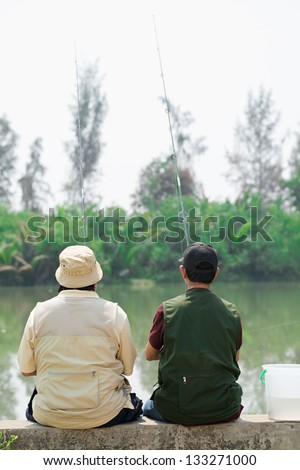 Rear view of two fishers waiting for fish - stock photo