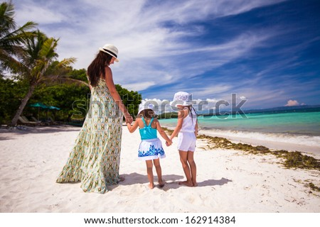 Rear view of two girls and their mother on a white, tropical beach - stock photo