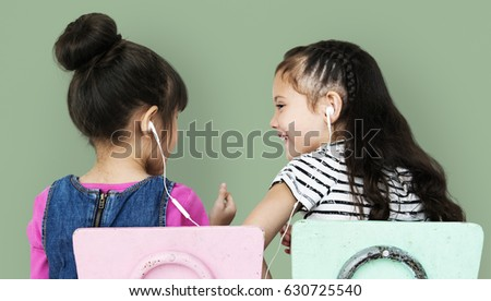 Rear view of two girls listening to music