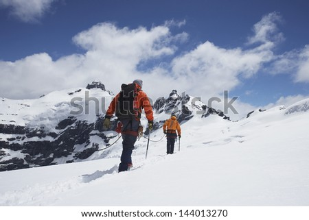 Rear view of two hikers joined by safety line in snowy mountains - stock photo