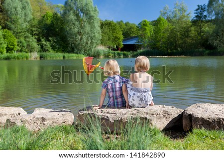 Rear view of two little blond girls sitting close together side by side on a rock fishing at the lake with a small net - stock photo