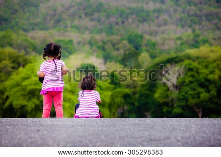 Rear view of two little girl at park