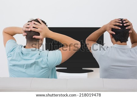 Rear view of two tensed soccer fans watching tv - stock photo