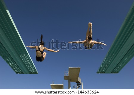 Rear view of two women diving from diving boards against clear blue sky - stock photo