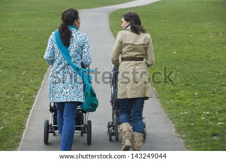 Rear view of two young mothers pushing strollers in park - stock photo