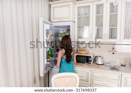Rear View of Unidentifiable Brunette Woman Standing in front of Open Refrigerator Door in White Kitchen at Home