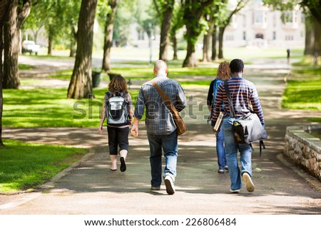 Rear view of university students with backpacks walking on campus road - stock photo