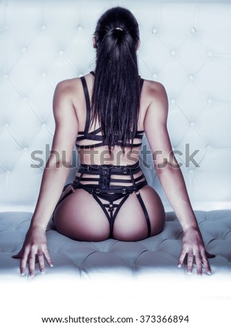 Rear View of Unrecognizable Woman with Long Dark Hair in Ponytail Wearing Strappy Bondage Lingerie and Sitting on Cushion While Leaning Back with Arched Back - Sexy Boudoir Portrait - stock photo