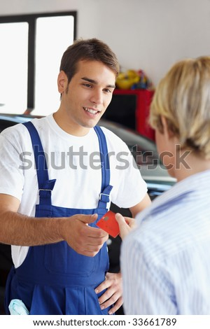 Rear view of woman giving credit card to mechanic.