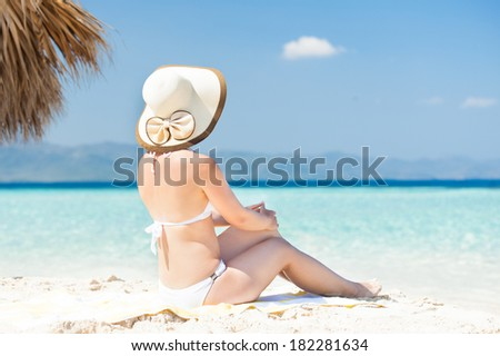 Rear view of woman in bikini enjoying the ocean view while sitting on beach towel - stock photo
