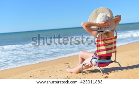 Rear view of woman in chair on summer time sun light beach holiday location. Blue sunny background