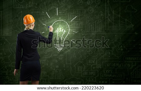 Rear view of woman in hardhat drawing sketches on blackboard - stock photo