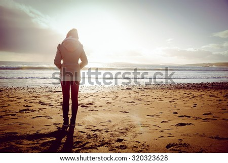 Rear view of woman looking at the sea during the sunset on the beach in front of camera - stock photo