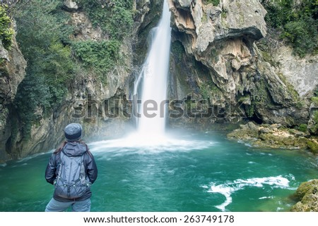 Rear view of Woman looking at waterfall - stock photo