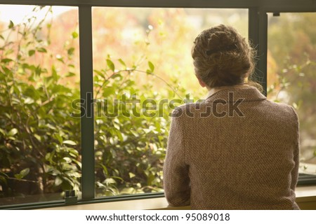 Rear view of woman looking out window - stock photo