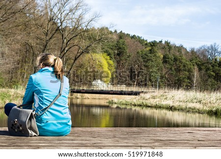 Rear view of woman relaxing in spring scenery over river on pier
