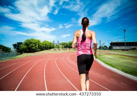 Rear view of woman running against white background against high angle view of track