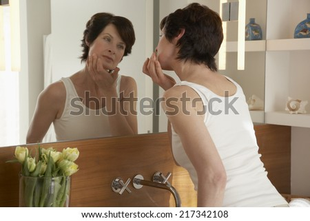 Rear view of woman standing in front of a mirror