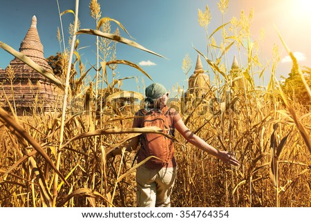 Rear view of woman traveler with a backpack walking through the field to the ancient Buddhist stupas. Myanmar.Concept of travel and adventure in Asia. - stock photo