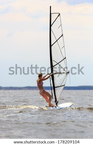 Rear view of woman windsurfing in splashes of water