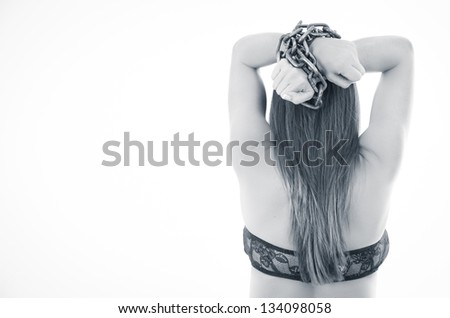 Rear view of woman with perfect body tied with a chain. Isolated over white - stock photo