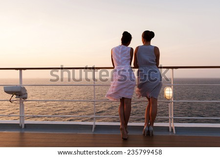 rear view of women looking at sunrise on a cruise ship - stock photo