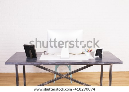 Rear view of workplace with computer monitor, picture frames and other items on wooden floor and white brick background