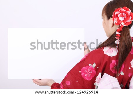 Rear view of young asian woman in traditional clothes of kimono holding a blank board - stock photo