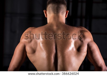 Rear view of young attractive caucasian muscular bodybuilder man with perfect body working out in fitness center, posing, showing back muscles, body sculpture concept