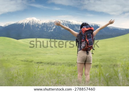 Rear view of young backpacker standing on the meadow while enjoying fresh air and mountain view - stock photo