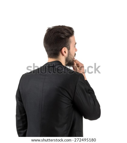 Rear view of young bearded guy looking at blank copy space white wall isolated. - stock photo