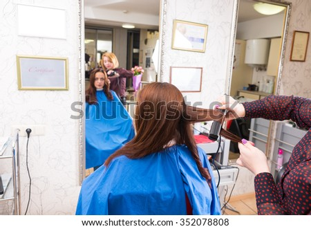 Rear View of Young Blond Stylist Using Flat Iron on Long Hair of Female Brunette Client in Salon with Blurred Reflection in Large Mirror in Background